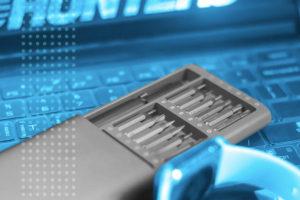 caixa de chaves de fenda e um apple watch sobre um teclado de notebook