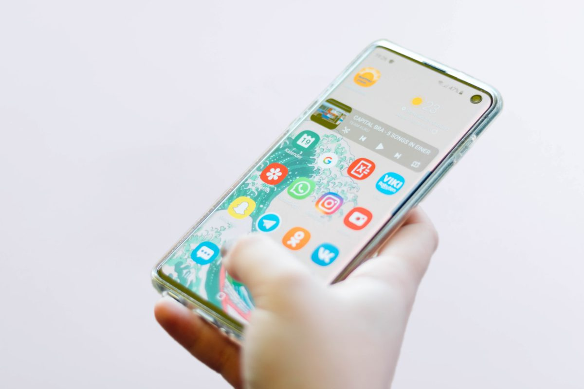 mão segurando celular com a tela mostrando os apps