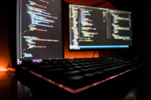 monitores exibindo códigos de programação